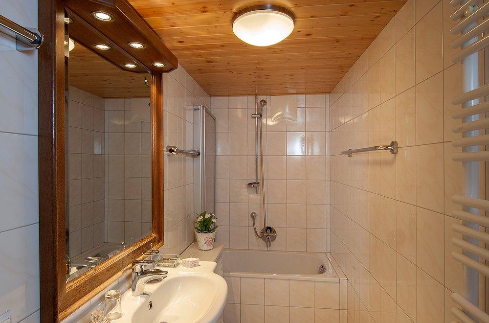 Badezimmer mit Badewanne, Waschtisch und Spiegel Chalet Dorfbäck