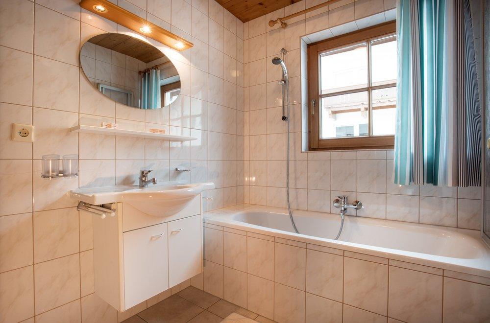 Blick auf Badewanne, Waschtisch und Spiegel im Badezimmer Apartment Alpenrose