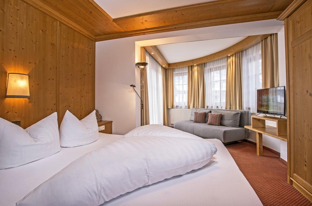 Schlafzimmer mit Fensterfront und Sofa Apartment Hochzillertal