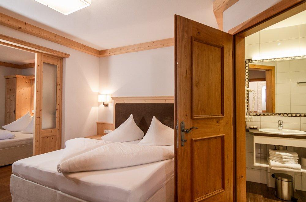 Schlafzimmer mit Boxspringbett und Blick auf das Badezimmer Apartment Panorama