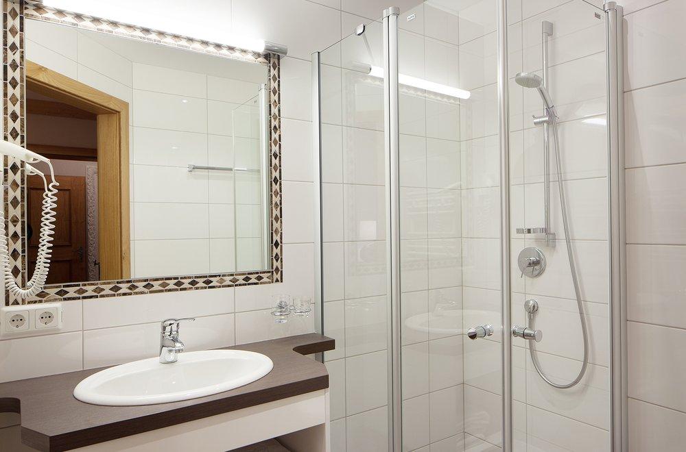 Badezimmer mit Dusche, Waschtisch, Spiegel und Toilette Apartment Schwalbennest