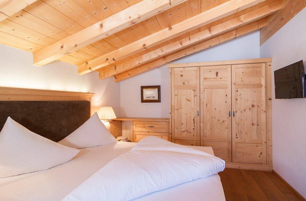 Zirbenschlafzimmer mit Boxspringbett im Dachgeschoss Apartment Schwalbennest