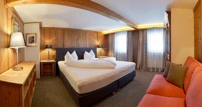 Schlafzimmer mit Boxspringbett und Sofa