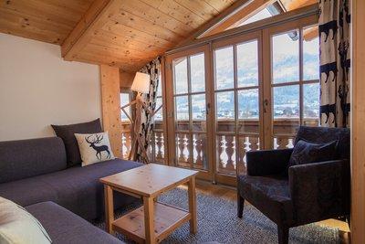 Wohnzimmer mit Ecksofa, Sessel und Fensterfront