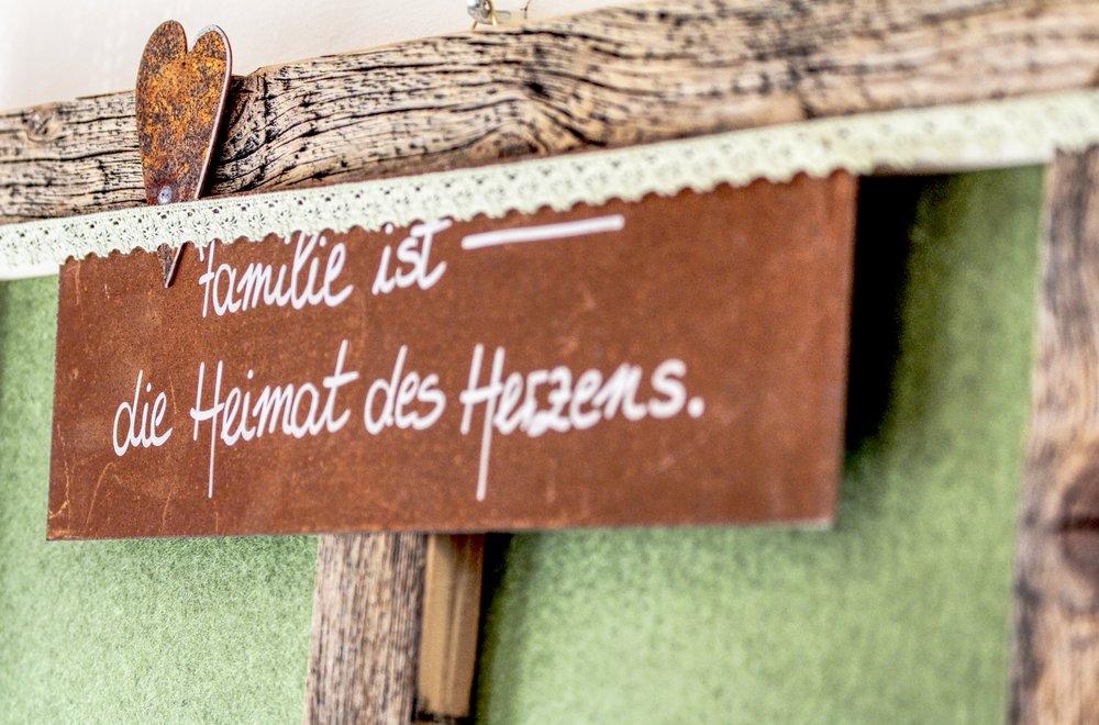 Schild mit der Aufschrift Familie ist - die Heimat des Herzens