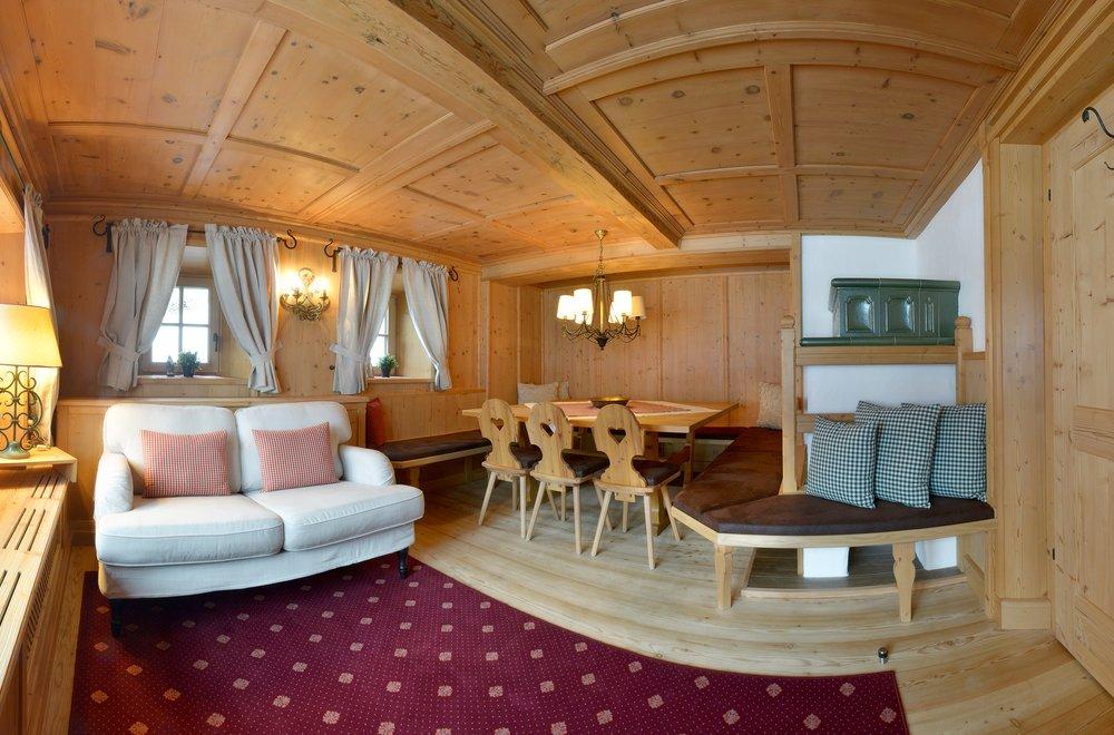 Blick auf Stube mit Sitzecke, Sofa und Kachelofen Chalet Dorfbäck