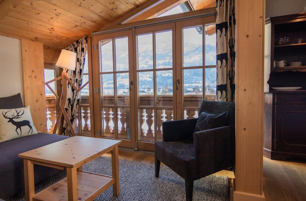 Wohnzimmer mit Sofa, Sessel und Fensterfront Apartment Schwalbennest