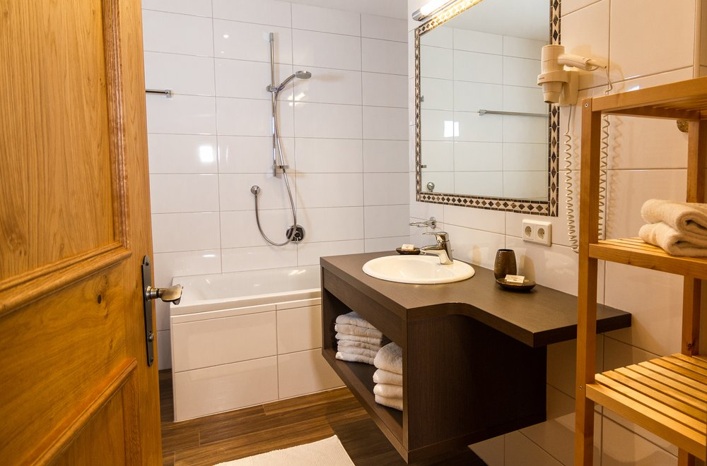 Badezimmer mit Badewanne, Waschtisch und Spiegel Apartment Schwalbennest