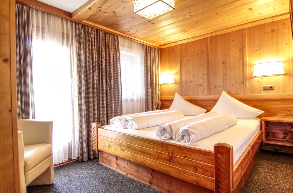 Schlafzimmer mit rustikalem Bett Chalet Dorfbäck
