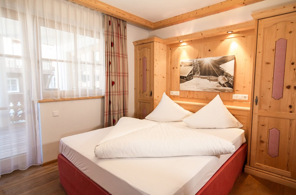 Schlafzimmer mit rotem Boxspringbett Apartment Tirol