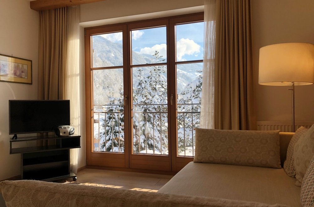 Wohnzimmer mit Fensterfront und Sofa Apartment Gerlosstein