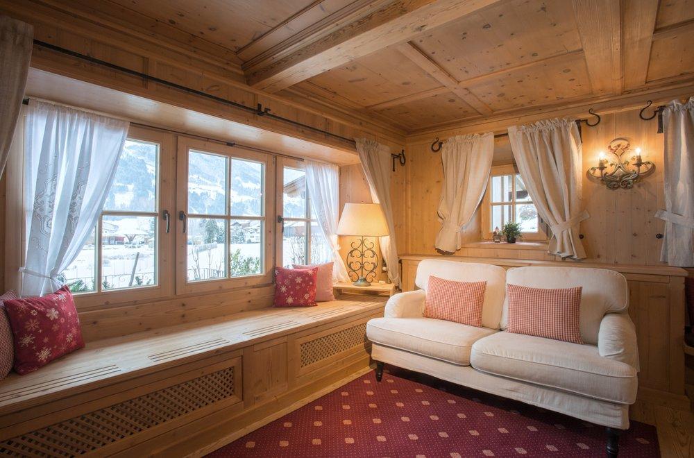 Stube mit Sofa und Fensterreihe Chalet Dorfbäck