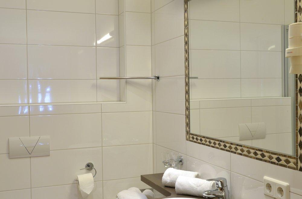 Badezimmer mit Toilette, Waschtisch und Spiegel Apartment Gänseblümchen