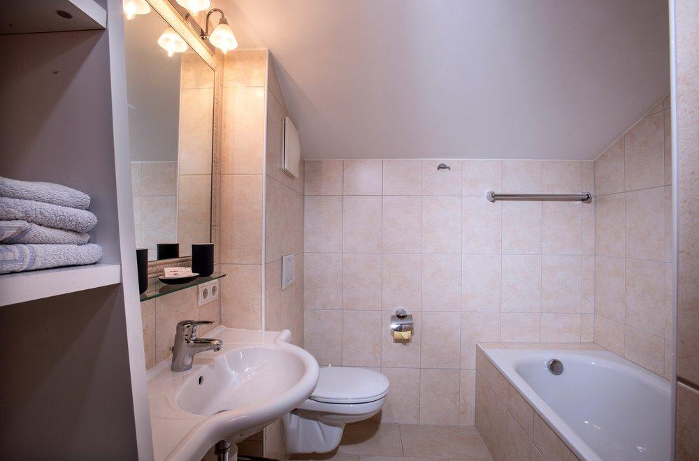 Badezimmer mit Toilette, Badewanne, Waschtisch und Spiegel Apartment Hochzillertal