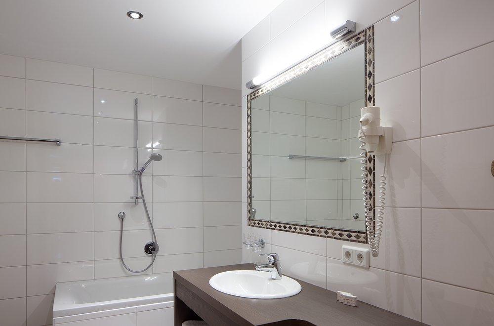 Badezimmer mit Badewanne, Waschtisch und Spiegel Apartment Tirol