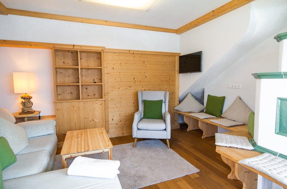 Wohnbereich mit Sessel und Kachelofen Apartment Tirol