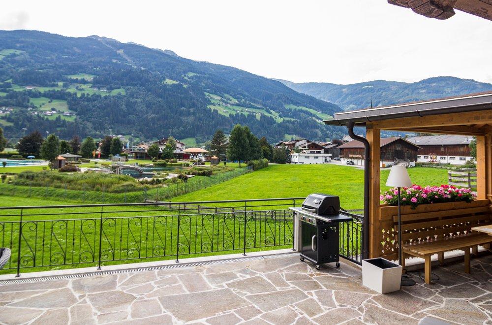 Terrasse mit Ausblick auf das Schwimmbad, Grill und Sitzecke Chalet Dorfbäck