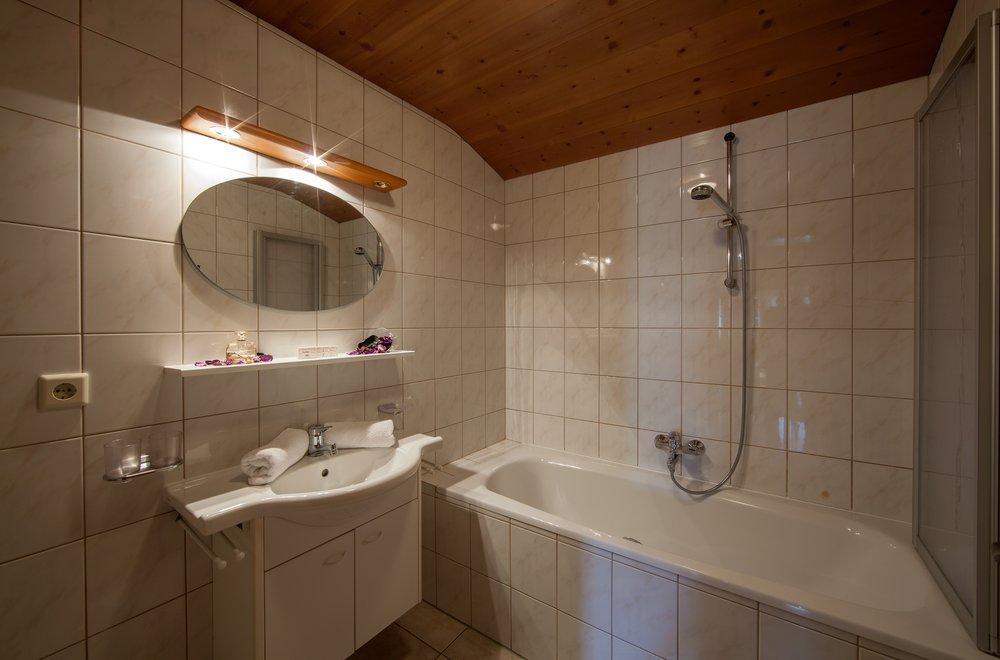 Badezimmer mit Badewanne, Waschtisch und Spiegel Apartment Enzian