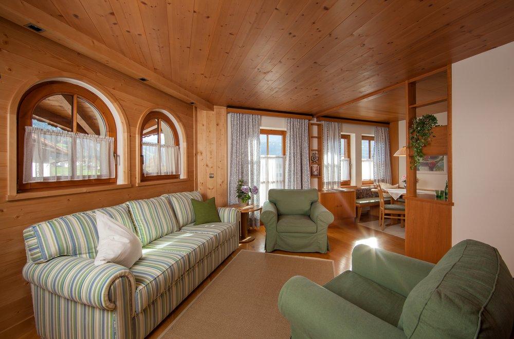 Wohnzimmer mit Sofa, zwei Sesseln und Blick auf Essbereich