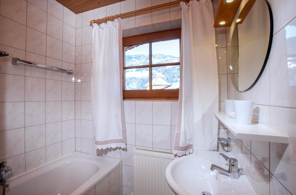 Badezimmer mit Badewanne, Waschtisch und Spiegel Apartment Lavendel