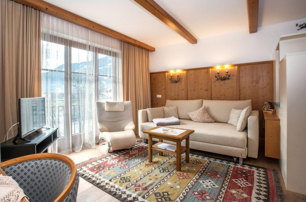 Wohnzimmer mit Fensterfront, Sofa und einem Sessel Apartment Gerlosstein